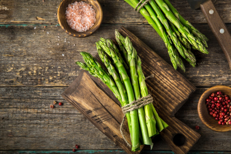 A wooden board with a bundle of asparagus, next to another bundle