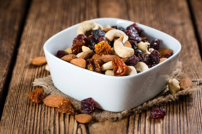 A white square bowl, with trail mix that includes nuts and dried fruit