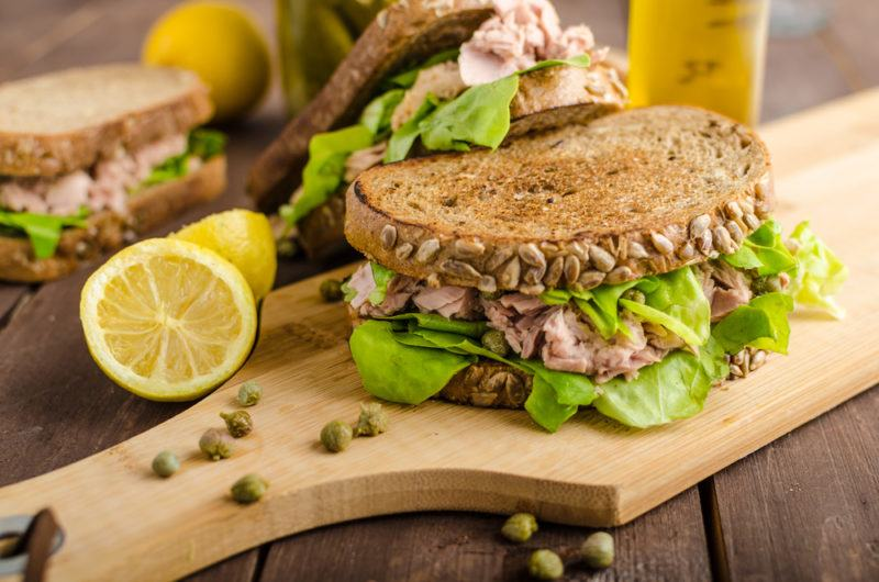 A wooden board with a tuna salad sandwich and a few in the background
