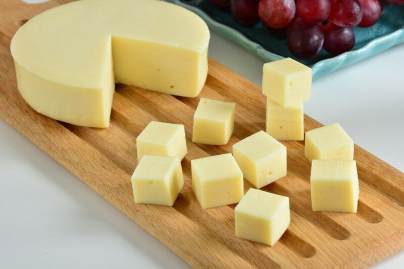 A wooden board with a wheel of cheese with a wedge cut out of it, and cubes of cheese