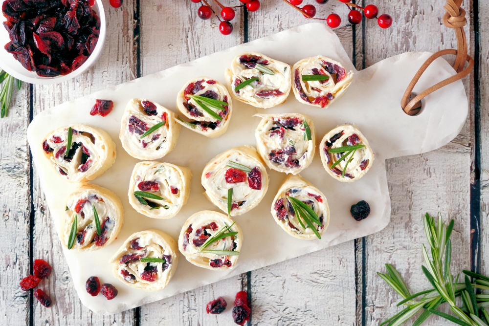 A white plate with cream cheese and cranberry pinwheels, with seasonal garnishes scattered around