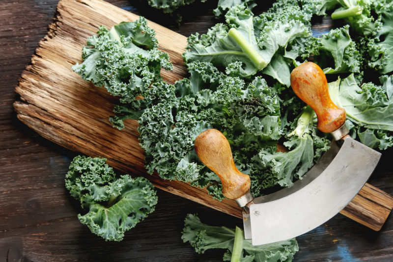 A wooden board with grains, with curly kale and a knife for chopping