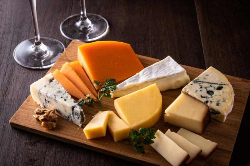 A wooden board with a selection of different hard cheeses