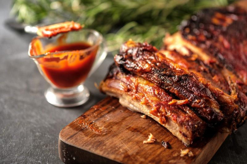 A wooden board containing pork ribs covered in glaze, next to a glass jug of glaze