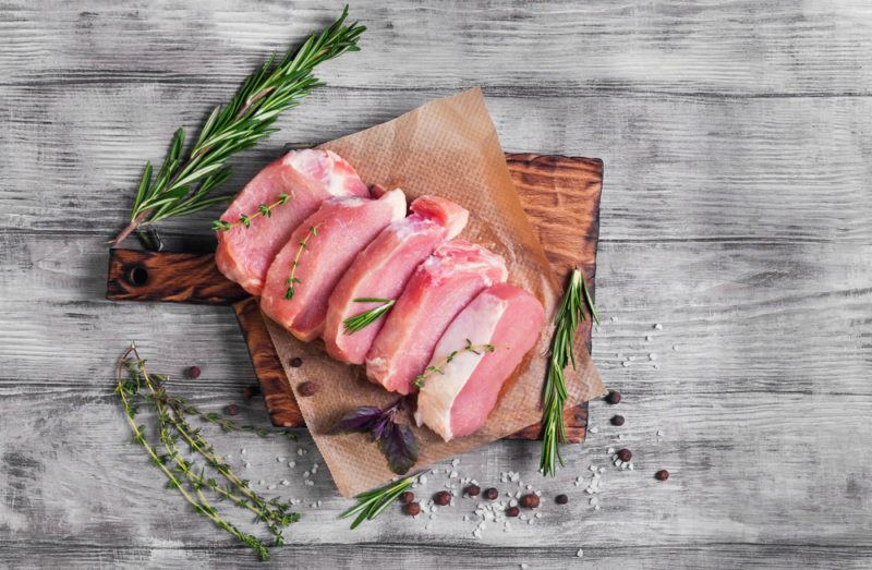Sliced pork with greenery on a wooden board on a table