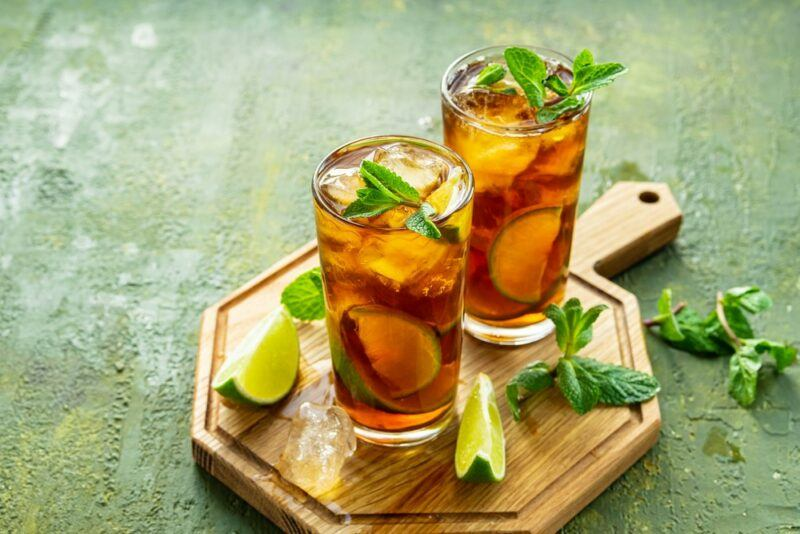 Two glasses of sparkling iced tea on a wooden board with some limes