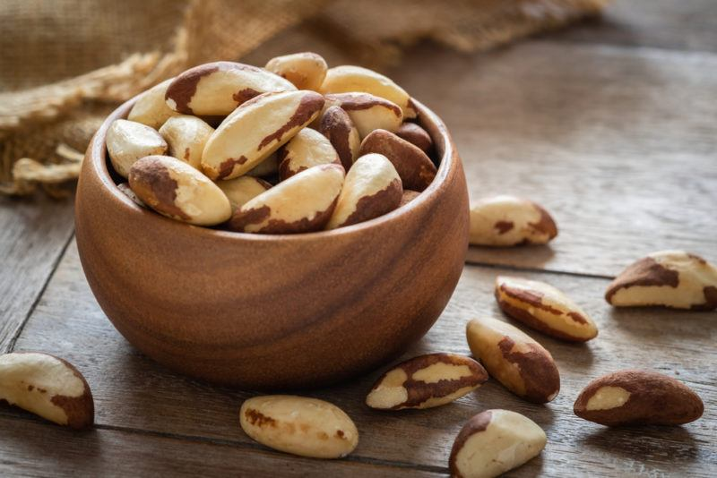 A small brown wooden bowl with Brazil nuts and more brazil nuts on the boards