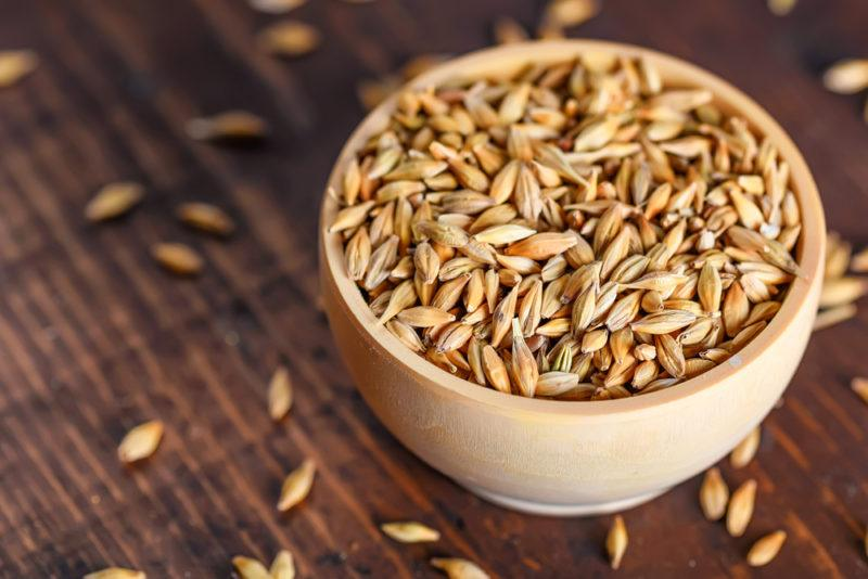 A small wooden bowl of barley with more spilling out onto the table