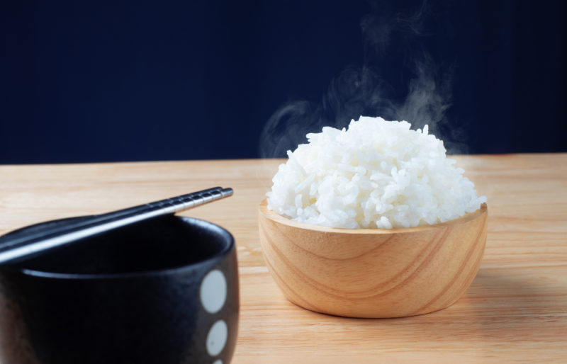 A small wooden bowl of cooked rice in front of a black bowl with chopsticks
