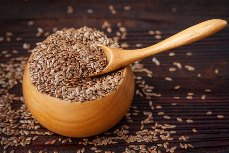 A brown bowl that contains flax seeds and a spoon