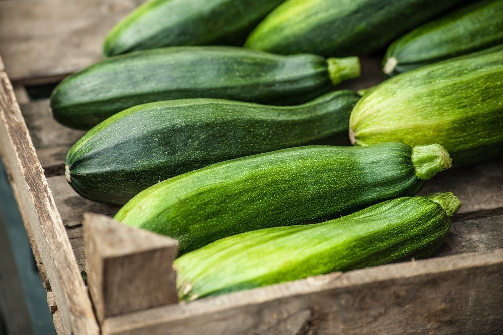 A wooden crate with fresh zucchinis