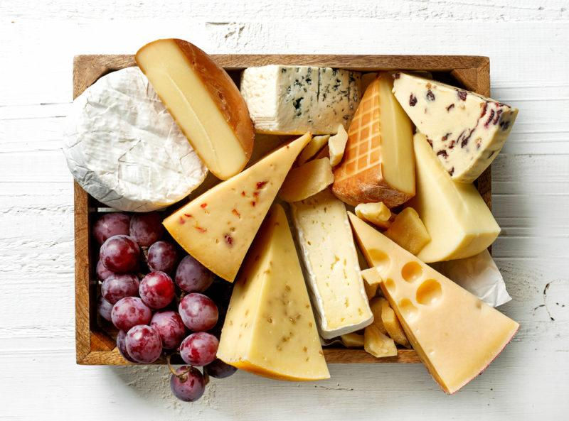 A wooden box filled with a selection of cheeses and some grapes