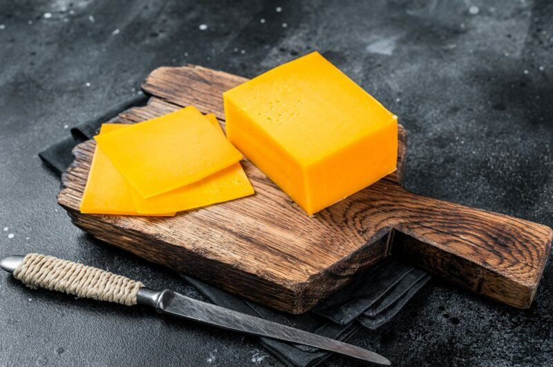 A wooden board with a large block of bright orange cheese and some slices