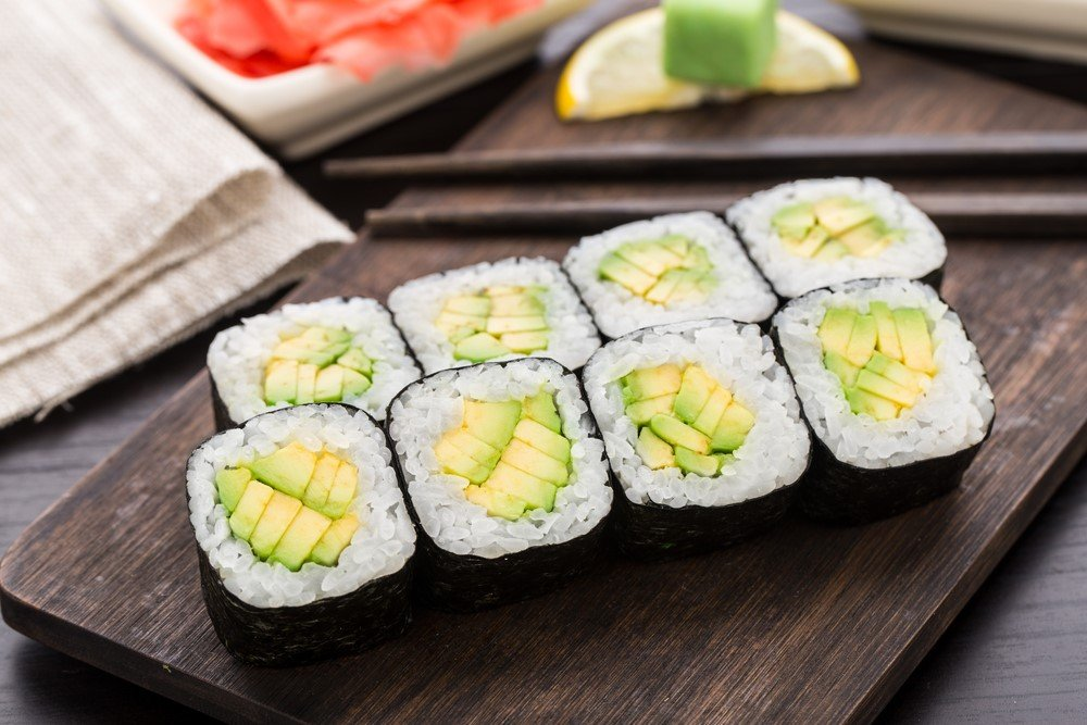 A wooden board with eight pieces of avocado sushi