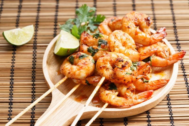 A wooden ladel with cooked shrimp on skewers