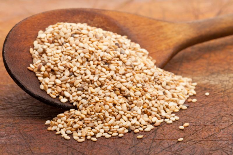 A wooden spoon filled with sesame seeds, with some spilling out onto the table