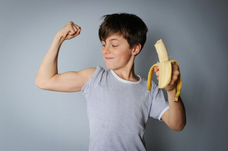 A young boy standing against a gray wall, holding a banana in one hand and flexing with the other