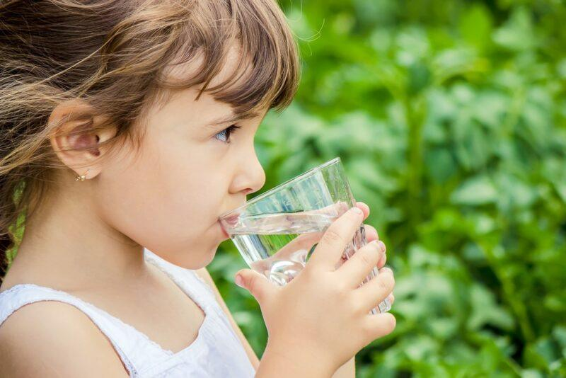 A young girl standing outside in front of greenery, drinking a glass of water