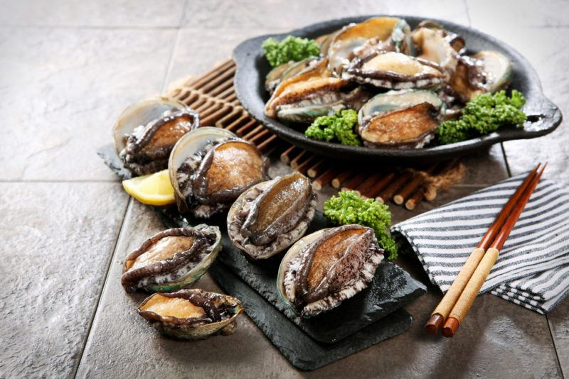 A black dish of ready to eat abalone, with more on the table and some chopsticks