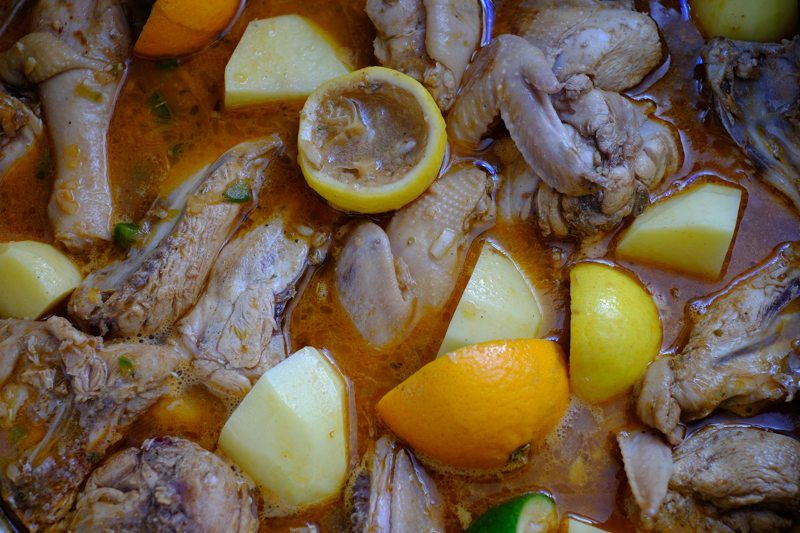 chicken with potatoes, lemon rinds, and meat juices