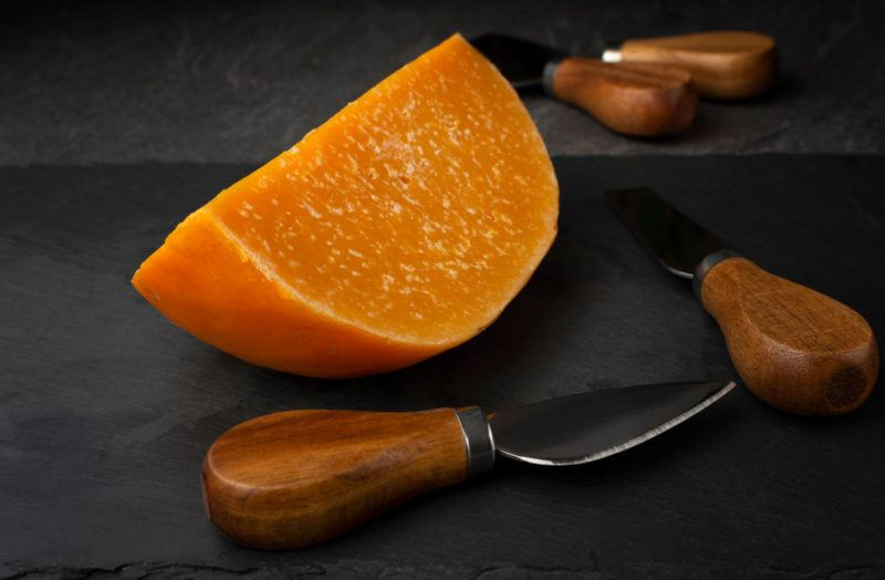 A wedge of aged gouda with various utensils