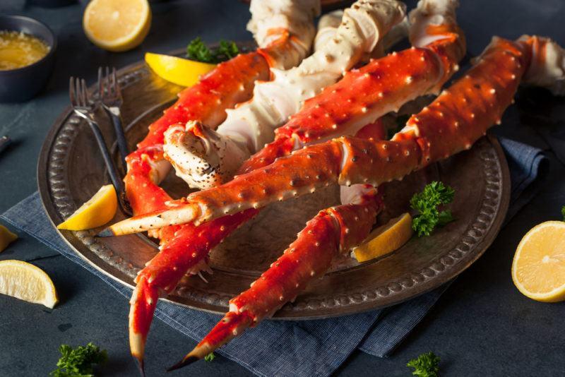 A black plate with fresh Alaskan king crab legs