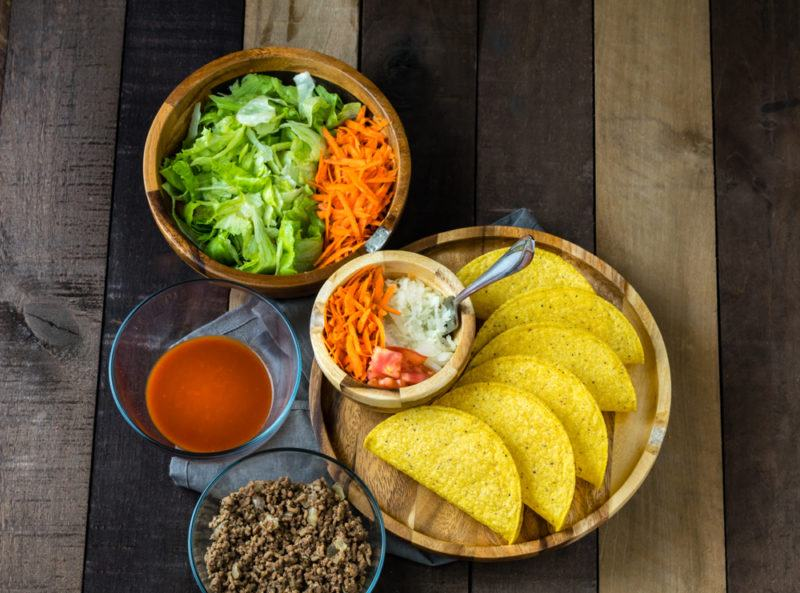 Multiple dishes with the ingredients to make homemade tacos
