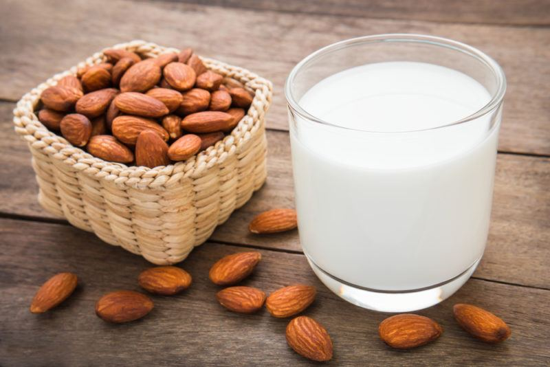 A glass of almond milk with a basket of almonds next to it