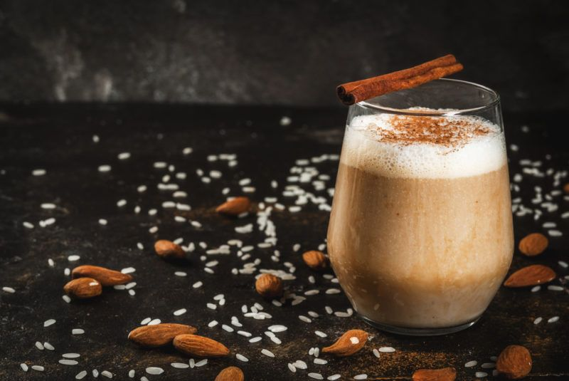 A mug of almond milk with cinnamon and coconut