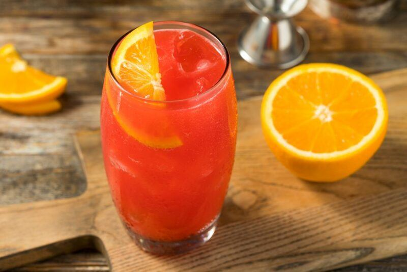 A wooden board with an Alabama slammer cocktail and half an orange, with a jigger and an orange wedge on the table