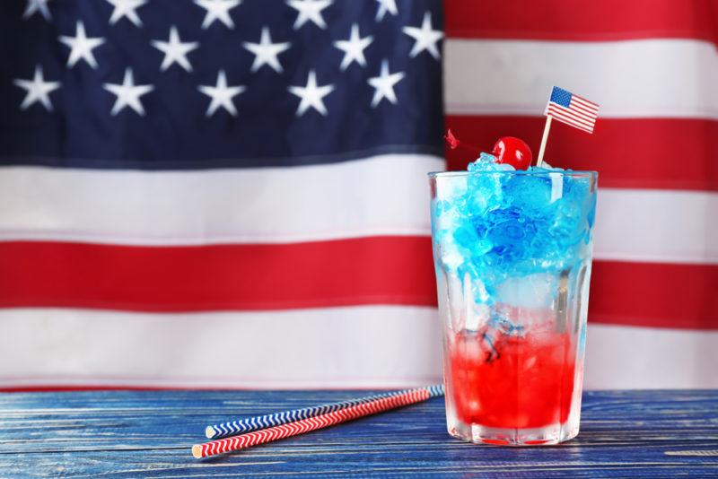 An American flag cocktail with a fully American flag in the background
