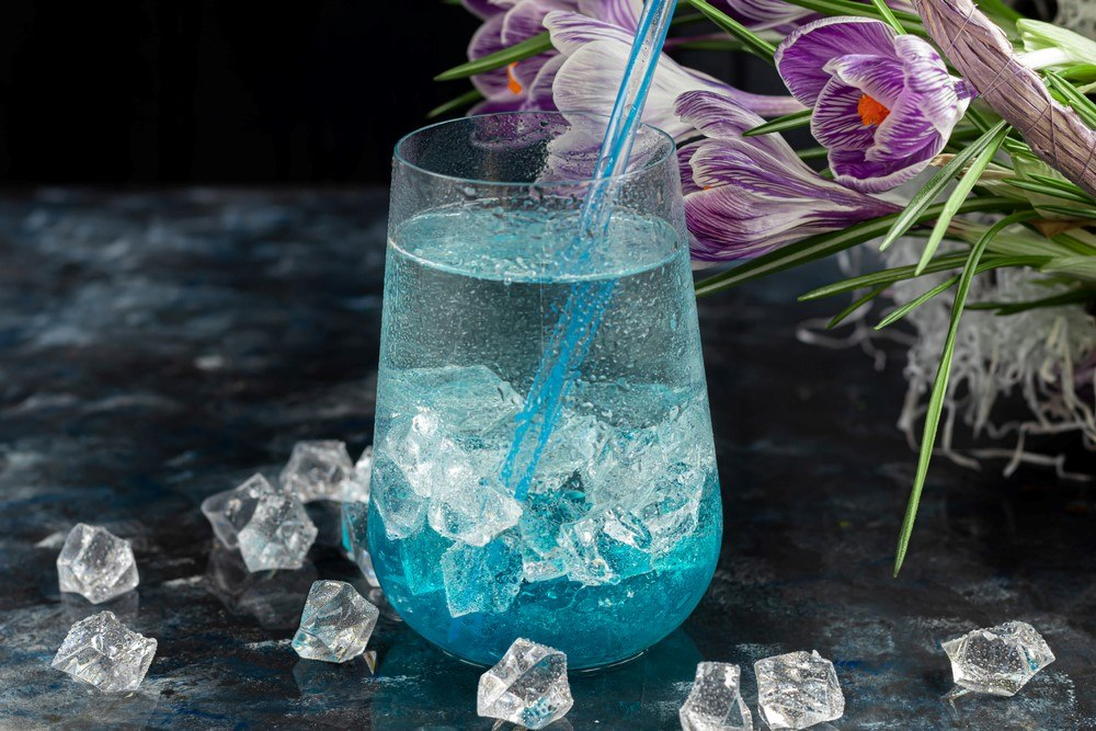 A stemless wine glass with a blue cocktail that contains ice