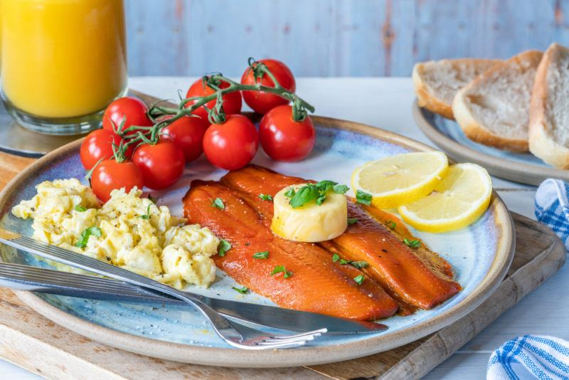 An English breakfast with kippers, eggs, tomoatos, lemons, butter and orange juice