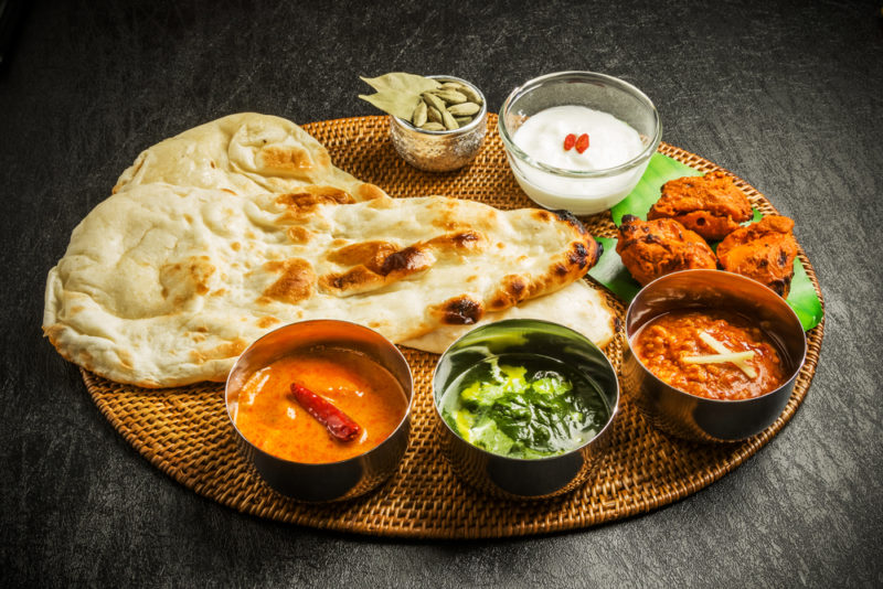 A wooden tray with naan bread, sauces, and curries