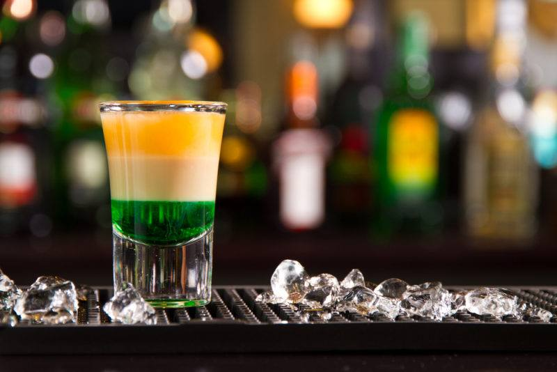 A three-layer Irish flag shot with an out-of-focus bar in the background