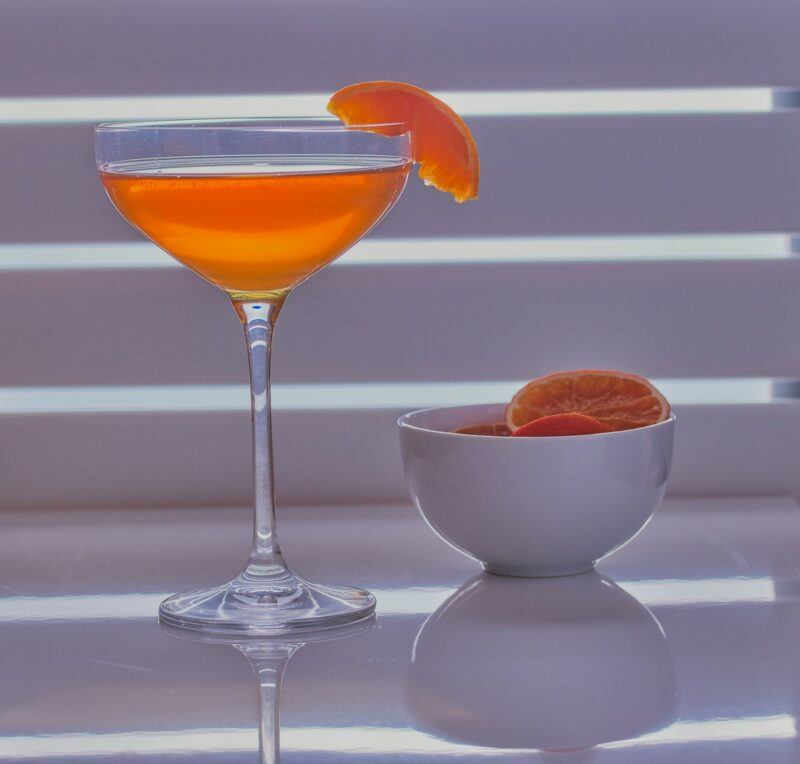 A martini glass with an Abbey cocktail and a bowl of oranges