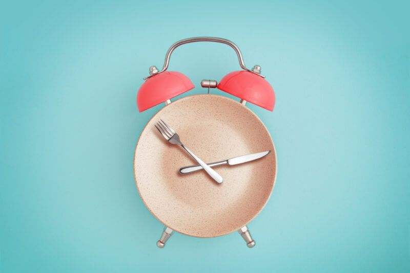 An alarm cock made using a plate, knife and fork, on a light blue background