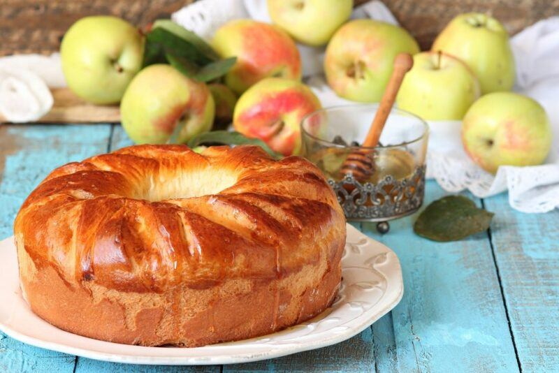 A white plate with an apple cake, in front of many green apples and a jar of honey