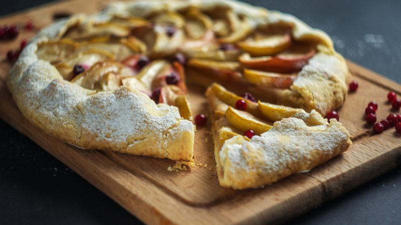 An apple and cranberry tart on a wooden board