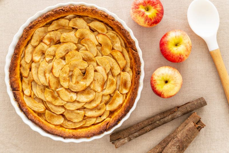 A fresh apple tart on a table next to three apples and a spoon