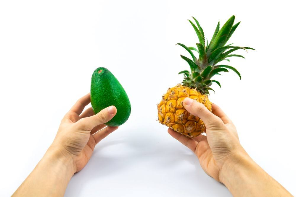 A pair of hands, one holding avocado and the other holding pineapple