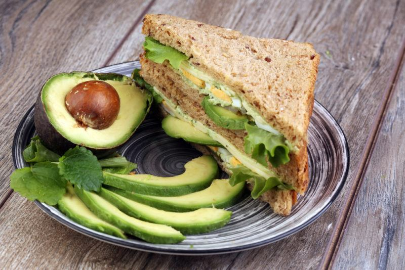 A plate containing an avocado and spinach sandwich, next to some avocado slices and an avocado half