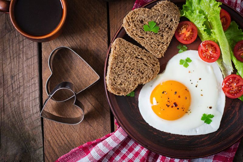 A brown plate with a love heart egg, two pieces of love heart toast, and veggies, on a wooden table next to the heart cutters used