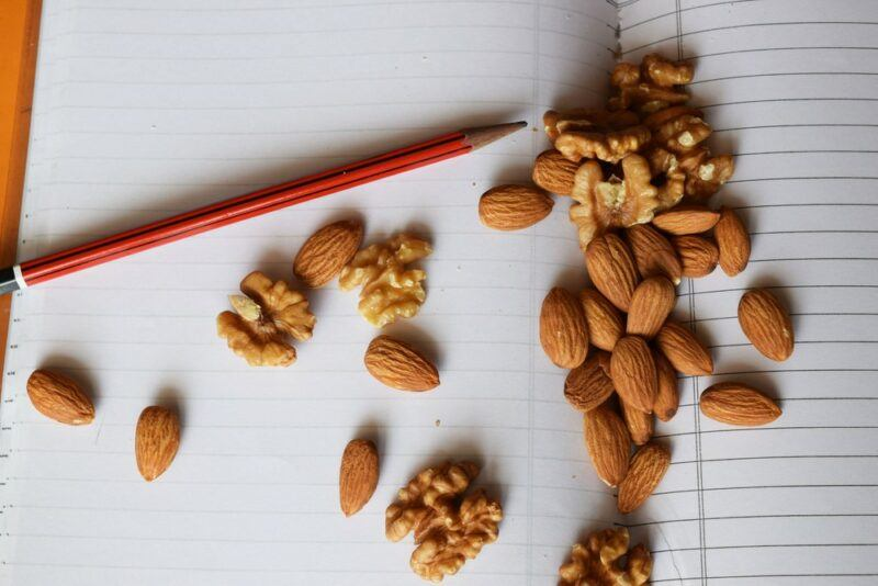 A school book with almonds and walnuts scattered across it, along with a red pencil
