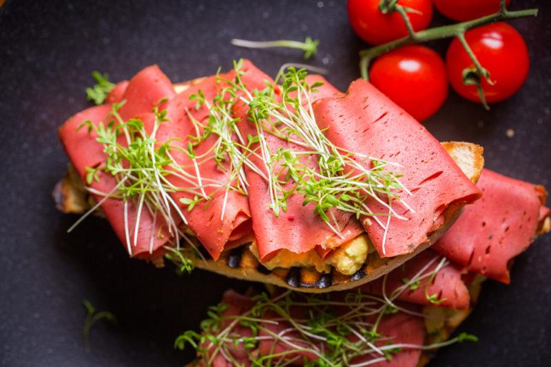 An open faced sandwich made using vegan ham with cress and some tomatoes in the background