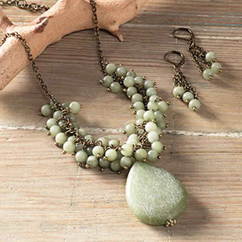 Green beaded necklace with matching earrings laid out on a wooden table