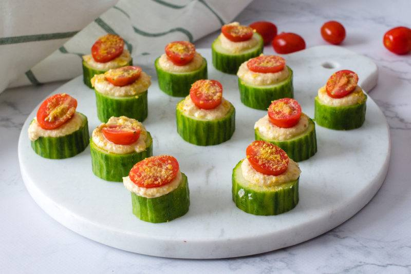 A marble cutting board with cucumber rounds that each have hummus and half a cherry tomato to make appetizers