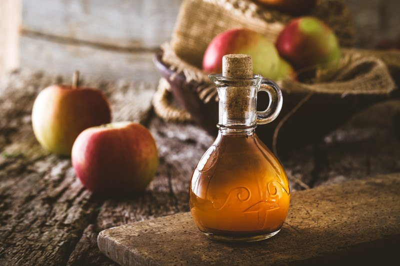 A flask of apple cider vinegar rests on a wooden board near a basket of apples and two loose apples.