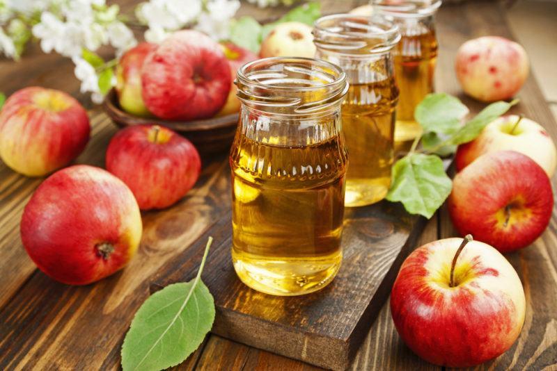 Apple juice in jars next to apples