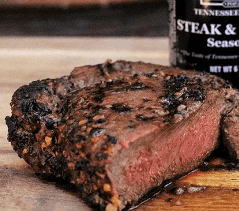 A medium rare steak seasoned and grilled, cut in half displaying the pink interior, in the background a bottle of steak seasoning
